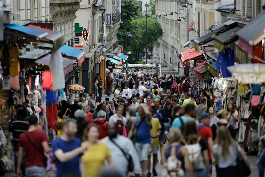 People, mainly tourists, throng a street in the Montmartre district of Paris.