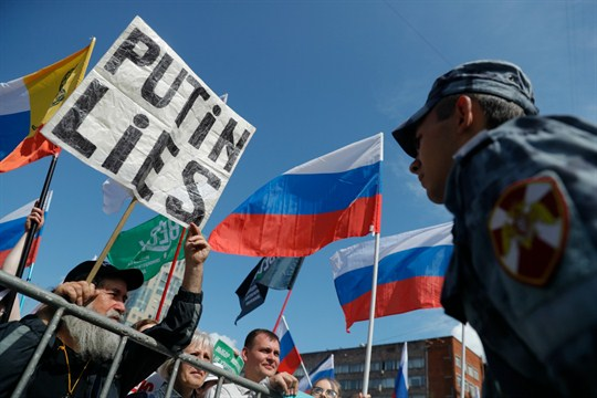 Protesters with flags stand in front of a police line during a protest in Moscow.