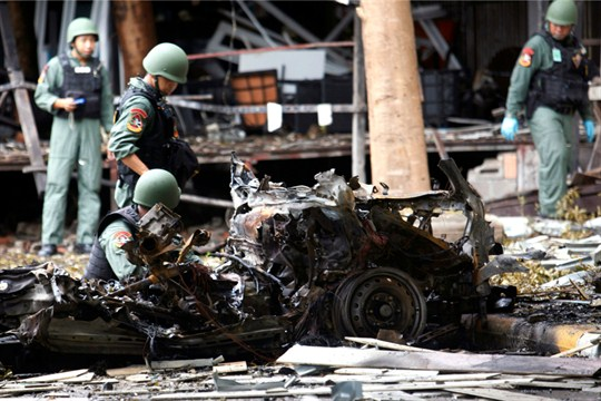 Thai bomb squad officers examine the wreckage of a car after an explosion in southern Thailand.