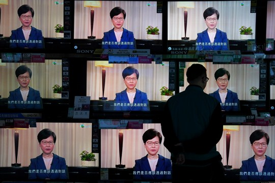 A man watches the television as Carrie Lam makes an announcement on the extradition bill.