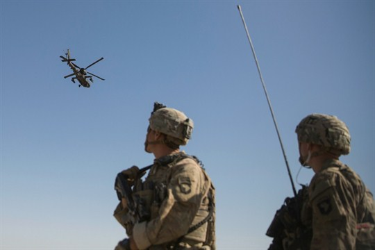 An AH-64 Apache attack helicopter provides security from above to U.S. soldiers at Bost Airfield, Afghanistan.