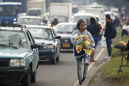 Amid rising Venezuelan immigration to Colombia, a migrant walks along a street in Bogota.