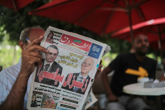 A man reads the Al-Shorouk daily newspaper showing candidates Kais Saied and Nabil Karoui.