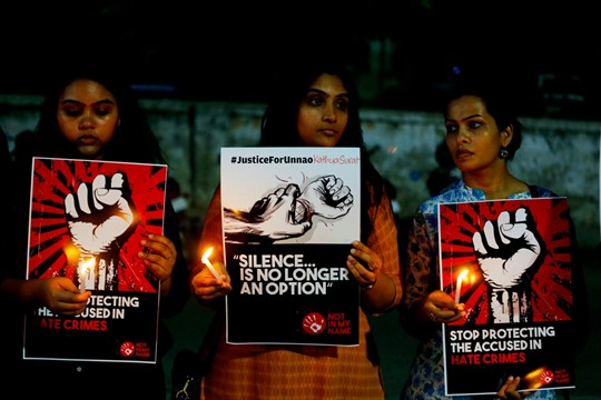 Indian women hold candles and posters during a protest against two recently reported rape cases.