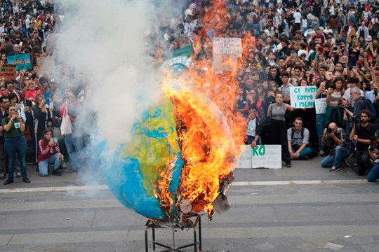 A replica Earth set ablaze in Italy during a worldwide protest demanding action on climate change.