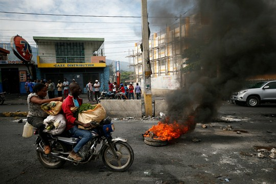 A motorcyclist drives past a burning barricade amid anti-government protests in Port-au-Prince, Haiti.