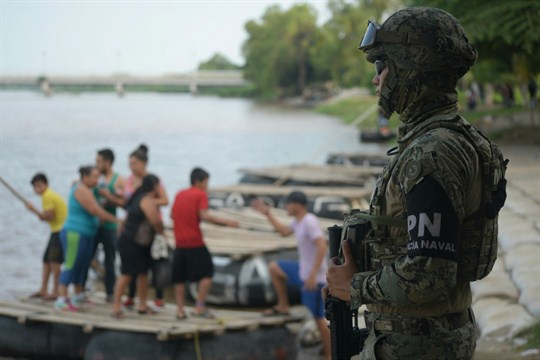 A Mexican marine stands guard at the Suchiate River border crossing between Guatemala and Mexico.