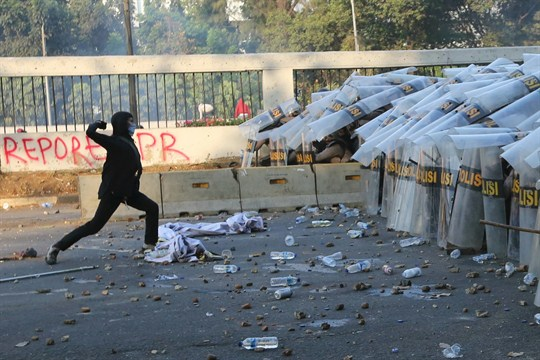 A student protester throws a rock at riot police during a clash in Jakarta, Indonesia.