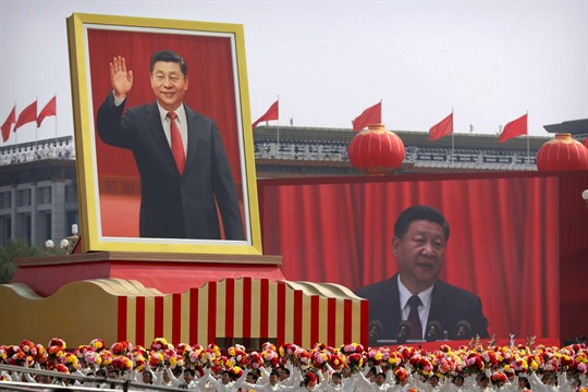 Crowds cheer beneath a large portrait of Chinese President Xi Jinping during China's National Day parade.