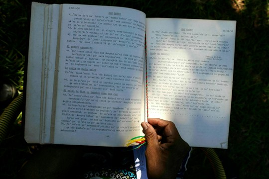 A Maka indigenous woman handles a copy of the Bible translated into her native language.