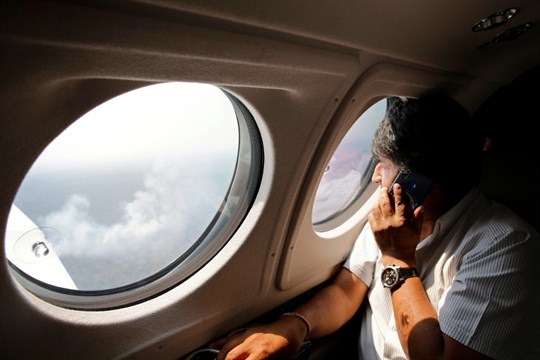 Bolivian President Evo Morales looks out of a plane window to survey forest fires