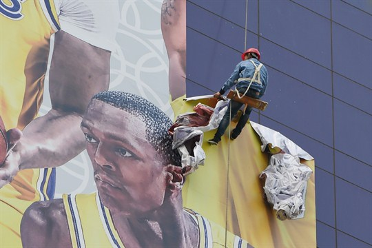 A worker tears down a poster promoting an NBA game in Shanghai.