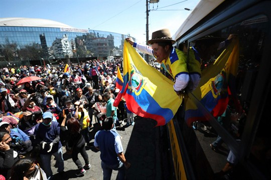 An anti-government protester waves a national flag from a bus in Quito.