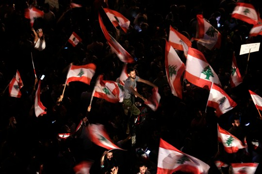 Anti-government protesters wave Lebanese flags during a protest in Beirut.