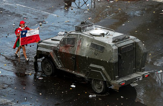 A Chilean protester faces off with an armored police vehicle during an anti-government march in Santiago.