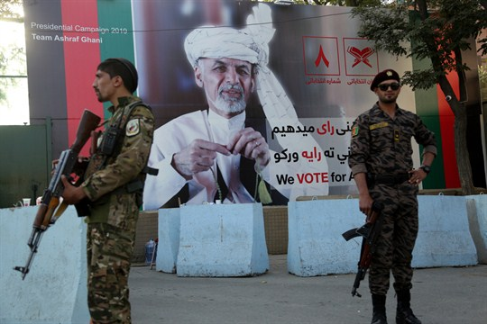 Afghan security forces stand guard near an election poster for President Ashraf Ghani in Kabul