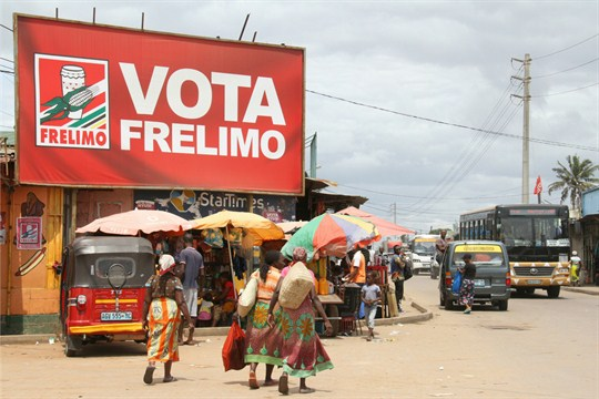 Women walk beneath an election banner for the ruling Frelimo party in Maputo, Mozambique.