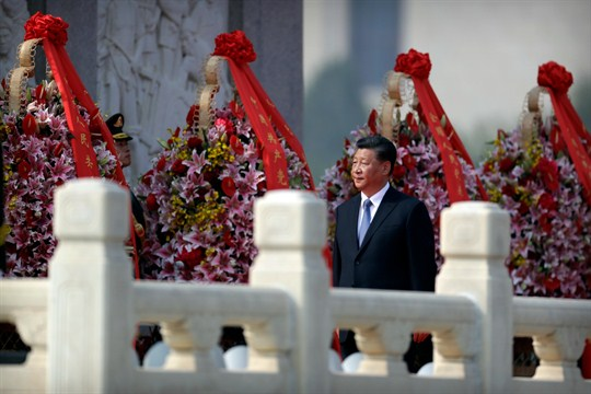 Chinese President Xi Jinping walks past floral wreaths at Beijing's Monument to the People's Heroes.