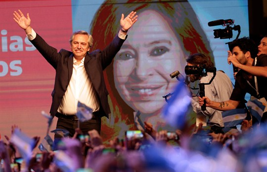 Argentine President-elect Alberto Fernandez waves to supporters in front of an image of Cristina Fernandez.
