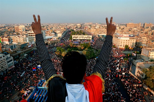 An Iraqi protester flashes the victory sign above an anti-government rally in Baghdad's Tahrir Square.