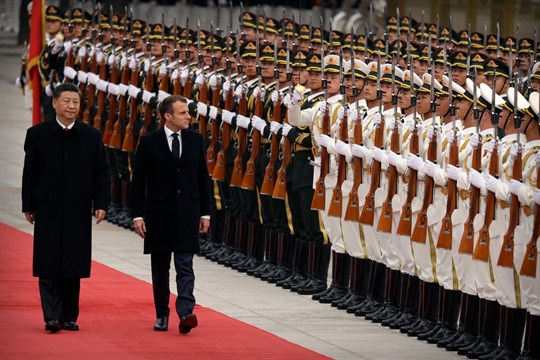 Xi Jinping and Emmanuel Macron review an honor guard during a welcome ceremony in Beijing.