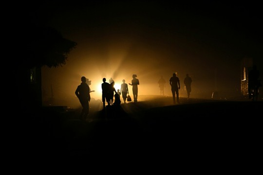 People walk home in the dark due to power shortages in Harare, Zimbabwe.