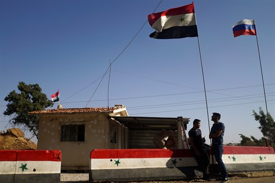 Syrian and Russian flags fly at a checkpoint of a de-escalation zone near Homs, Syria.
