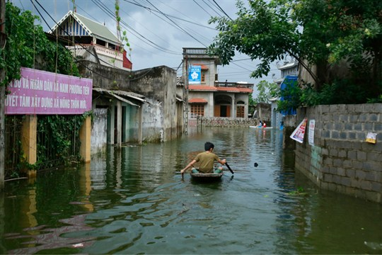 A man paddles a boat through a flooded village in Hanoi, Vietnam.