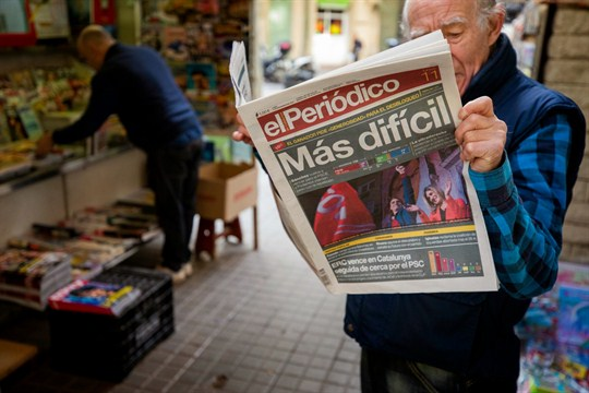 "A man reads a newspaper with the headline ""More Difficult"" at a newsstand in Barcelona."