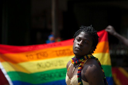 A transgender Ugandan poses in front of a rainbow flag in Etebbe, Uganda.