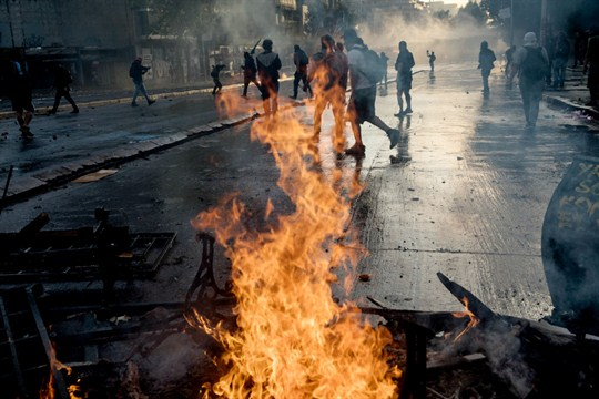 Anti-government protesters in Chile walk past a burning barricade set on fire during clashes with police
