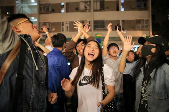 Pro-democracy supporters celebrate after pro-Beijing politician Junius Ho lost his election in Hong Kong