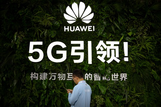 A man uses his smartphone at a display for Huawei 5G services at a Beijing expo.