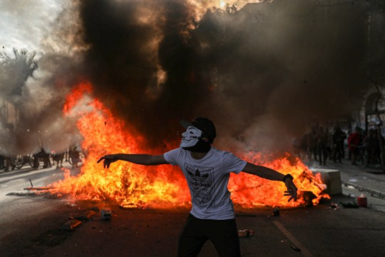 A demonstrator wearing a mask in front of a burning barricade during a protest in Chile