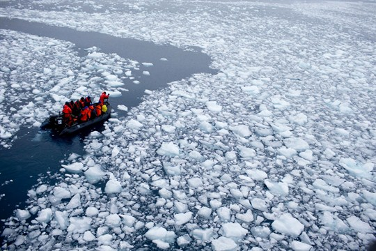 A zodiac carrying a team of international scientists heads to a research station Antarctica.