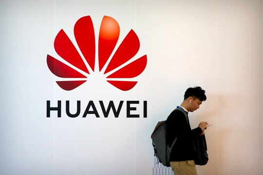 A man uses his smartphone as he stands near a billboard for Chinese technology firm Huawei
