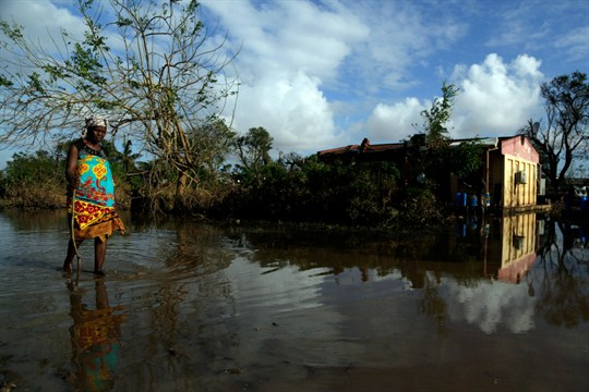 A woman walks along a flooded road in Buzi district, outside Beira, Mozambique