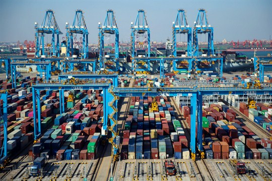 Trucks load containers at the automated container dockyard in Qingdao, Shandong province, China.