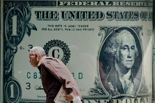 A man walks past a poster showing a U.S. dollar outside an exchange office in Cairo.