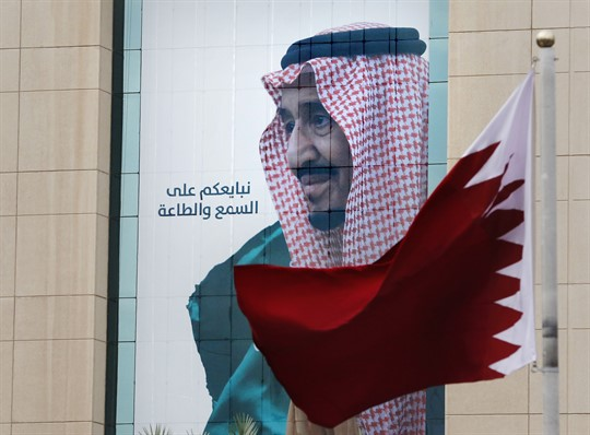 Qatar's flag over a banner showing Saudi Arabia's King Salman, whose country coordinated the Qatar blockade.