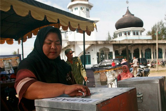 A woman casts her ballot at a voting station during a local election in Aceh Besar