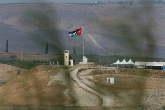Soldiers stand guard in a watchtower flying Jordanian flags near the Israeli-Jordanian border