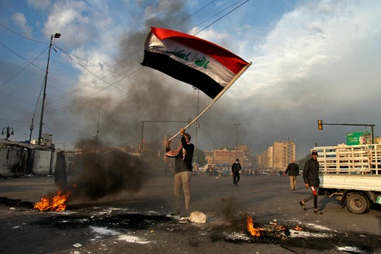 An Iraqi protester waves the national flag during a demonstration against an Iranian missile strike
