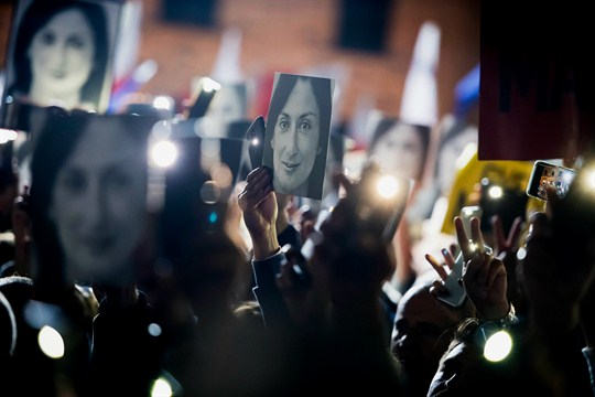 Protesters hold pictures of slain journalist Daphne Caruana Galizia outside Maltese Prime Minister Joseph Muscat's office