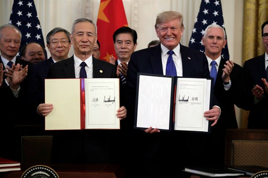 "President Trump and Chinese Vice Premier Liu He hold up the signed ""phase one"" trade deal"