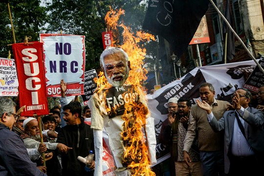 Demonstrators burn an effigy of Narendra Modi while protesting against a new citizenship law in Kolkata.