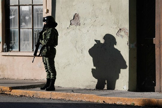 A member of the Mexican security forces stands guard near City Hall in Villa Union.