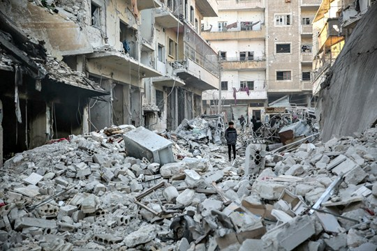 People inspect damaged buildings following three airstrikes targeting a hospital in Idlib.