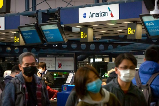 Travelers wearing face masks line up to check in for an American Airlines flight in Beijing.