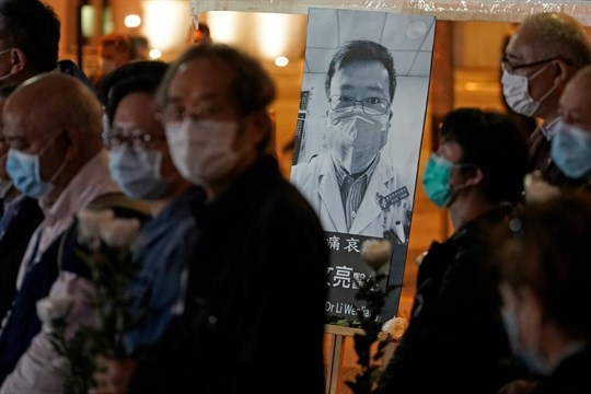 People wearing masks attend a vigil for Chinese doctor Li Wenliang, in Hong Kong